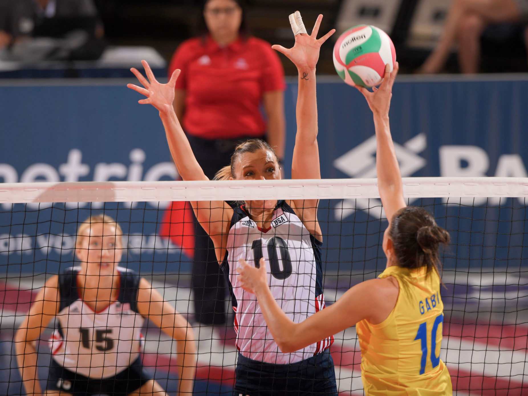 volleyball player jordan larson blocking at net